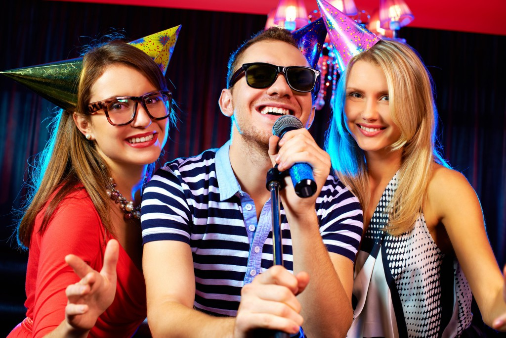 Portrait of happy friends singing in microphone in the karaoke b